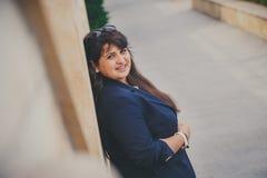 Lycklig le härlig överviktig ung kvinna i mörker - blått omslag utomhus på gatan Säker fet ung kvinna Xxl kvinna Royaltyfri Fotografi