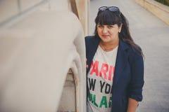 Lycklig le härlig överviktig ung kvinna i mörker - blått omslag utomhus på gatan Säker fet ung kvinna Xxl kvinna, p Royaltyfri Foto