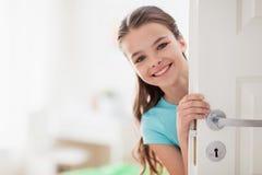 Lycklig le härlig flicka bak dörr hemma Arkivfoto