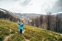 Lycklig le hög härlig kvinna för handelsresande i blå regnomslag och jeans i berg som omges av skogen som tycker om arkivbild