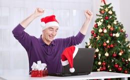 Lycklig le hög man med den Santa Claus hatten som direktanslutet shoppar Royaltyfri Foto