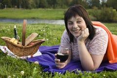 Lycklig le kvinna för mogen brunett med exponeringsglas av vin på picknicken som har gyckel, verkligt modernt folkbegrepp för liv arkivbilder
