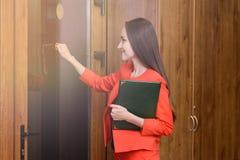 Lycklig le kvinna i en röd dräkt med dokument i hand som knackar på dörren till framstickandet Royaltyfria Bilder