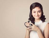 Lycklig le kvinna i tillfällig kläder som rymmer den vita koppen av coffe Arkivbild
