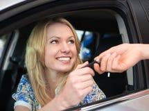 Lycklig le kvinna med biltangent i bil Arkivbild