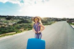Lycklig le kvinna med den blåa resväskan på en väg Royaltyfri Bild