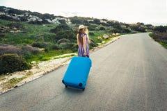 Lycklig le kvinna med den blåa resväskan på en väg Arkivfoto