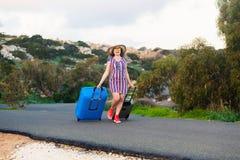 Lycklig le kvinna med den blåa resväskan på en väg Arkivbild