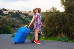 Lycklig le kvinna med den blåa resväskan på en väg Arkivfoton