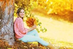 Lycklig le kvinna med gula lönnblad som sitter under träd i solig höst arkivfoto