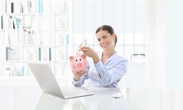 Lycklig le kvinna på datoren med kassa och spargrisen, bu royaltyfri foto