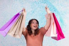 Lycklig le kvinna på shopping som rymmer färgrika pappers- påsar, pac Royaltyfri Bild