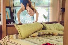 Lycklig le kvinna som är uppochnervänd i säng i sovrummet Arkivfoto