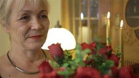Lycklig le kvinna som rymmer en stor bukett av röda rosor Födelsedag, moderdag, årsdag eller valentin stock video