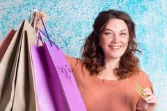 Lycklig le kvinna som rymmer pappers- påsar för färgglad shopping, bank Fotografering för Bildbyråer