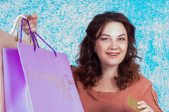 Lycklig le kvinna som rymmer pappers- påsar för färgglad shopping, credi Royaltyfri Foto