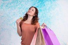 Lycklig le kvinna som rymmer pappers- påsar för färgrik shopping, bank c Royaltyfria Foton
