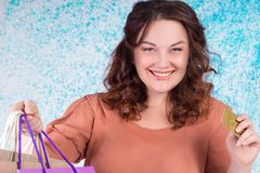 Lycklig le kvinna som rymmer pappers- påsar för färgrik shopping, kreditering Royaltyfria Bilder