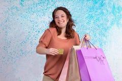 Lycklig le kvinna som rymmer pappers- påsar för mångfärgad shopping, b Arkivfoton