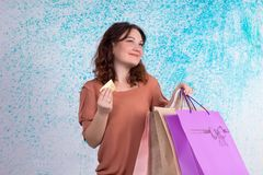 Lycklig le kvinna som rymmer pappers- påsar för mångfärgad shopping, b Royaltyfria Bilder