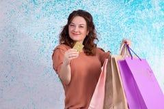 Lycklig le kvinna som rymmer pappers- påsar för mångfärgad shopping, lodisar Royaltyfri Bild