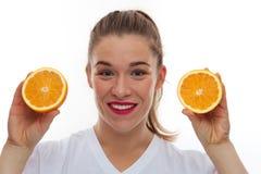 Lycklig le kvinna som rymmer två stycken av apelsiner royaltyfri foto