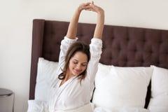 Lycklig le kvinna som sträcker i säng som upp vaknar otta arkivfoto