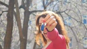 Lycklig le kvinna som utomhus rymmer hennes nya lägenhet- eller biltangenter i en hand med röd manikyr under vårtid på lager videofilmer
