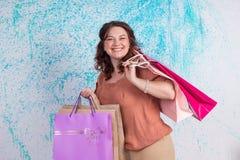 Lycklig le kvinna under shopping som rymmer färgglade pappers- påsar Arkivbilder