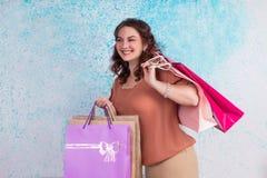 Lycklig le kvinna under shopping som rymmer färgrika pappers- påsar, Royaltyfri Foto
