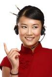 Lycklig le kvinnlig asiatisk kundtjänstoperatör Arkivfoto
