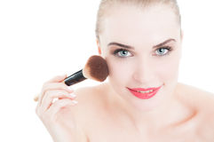 Lycklig le kvinnlig modell genom att använda sminkborsten royaltyfri foto