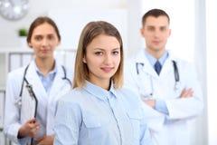 Lycklig le kvinnlig patient med två gladlynta doktorer i bakgrunden Läkarundersökning- och sjukvårdbegrepp royaltyfri bild