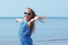 Lycklig le liten flicka i solglasögon på strandsemester Arkivbild