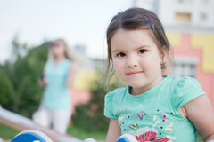Lycklig le liten flicka på lekplats Arkivfoton