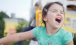 Lycklig le liten flicka på lekplats Royaltyfria Bilder