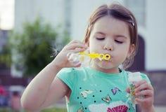 Lycklig le liten flicka på lekplats Arkivfoto