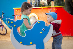 Lycklig le liten flicka på lekplats Fotografering för Bildbyråer