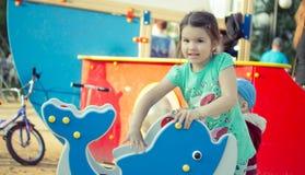Lycklig le liten flicka på lekplats Arkivbild