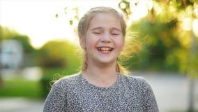 Lycklig le liten flickastående Skratta för härligt barn Flickan har mycket gyckel arkivfilmer