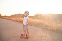 Lycklig le liten unge i sporthjälmanseende på solnedgångvägen med sparkcykeln Royaltyfri Foto