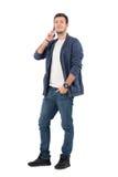 Lycklig le man i jeans och grov bomullstvillskjorta som talar på telefonen som ser kameran royaltyfri foto