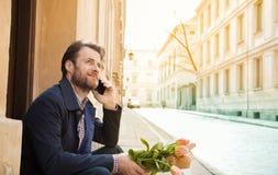 Lycklig le man med blommabuketten som talar på en mobiltelefon - stad Arkivbild