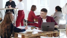 Lycklig le manlig affärschef som talar till den unga blonda kollegakvinnan som sitter på kontorstabellen sund arbetsplats arkivfilmer