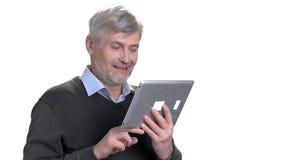 Lycklig le medelålders man som använder den digitala minnestavlan stock video