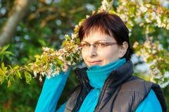 Lycklig le mellersta ålderkvinna som är utomhus- med trädet Arkivbilder