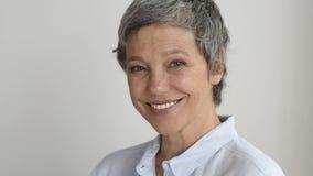 Lycklig le mogen kvinna på grå bakgrund lager videofilmer