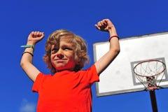 Lycklig le pojke som firar seger med händer i luften arkivfoto