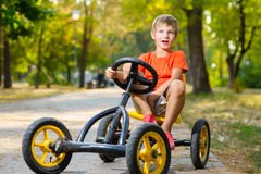 Lycklig le pojke som kör en leksakbil som är utomhus- i Arkivbild