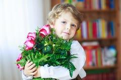 Lycklig le pys med blommande rosa rosor i grupp Arkivbild